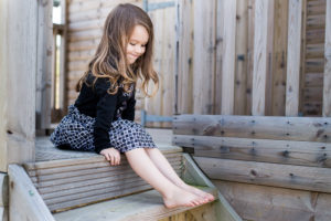 A little girl looks at her bare feet during an outdoor family photoshoot