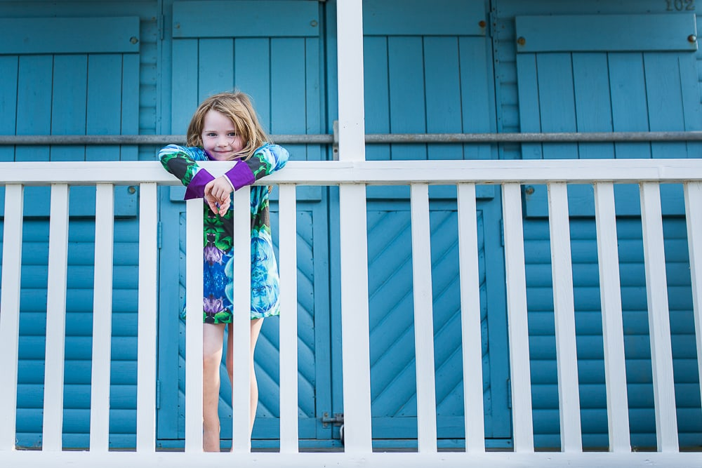 A girl hangs over the bar of a beach hut during an outdoor family photoshoot