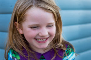 A girl giggles as part of an outdoor family photoshoot