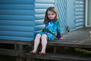 A girl wears a blue dress while sitting against a blue beach hut during an outdoor family photoshoot
