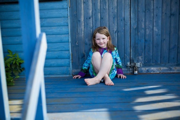 A girl sits down on a blue beach during a outdoor family photoshoot