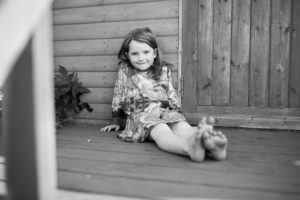 A girl poses on a beach hut as part of a children photographer photoshoot