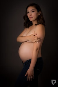 A pregnant lady smiles at the camera during her London maternity photographer session