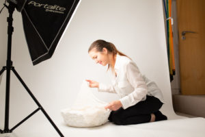 Muswell Hill photographer Louisa Peacock prepares a white set up for a newborn baby