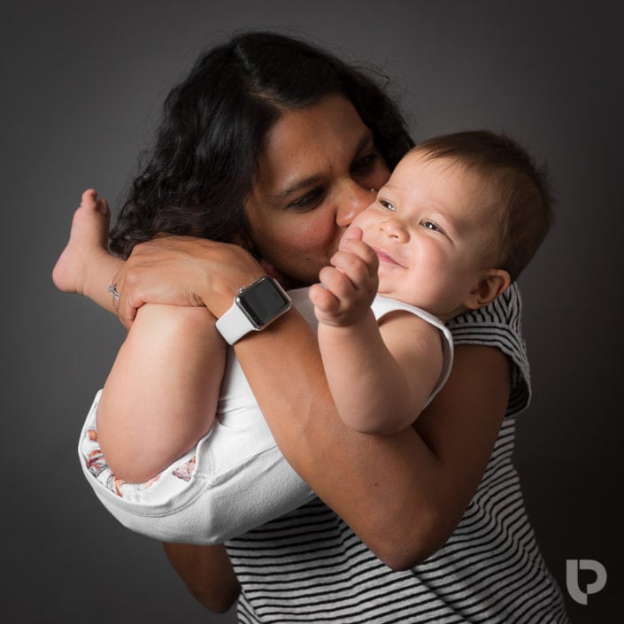 A mum cuddles her baby making him laugh during a studio based photoshoot