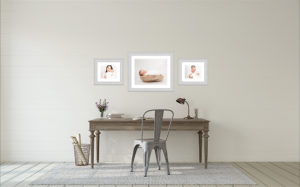 Three newborn photos hang on the wall after a North London photography session