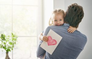 A dad carries his daughter during a family photography shoot