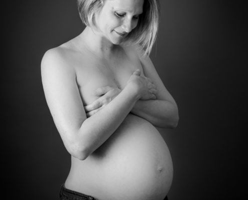 A delighted mama poses for her pregnancy photographer London session