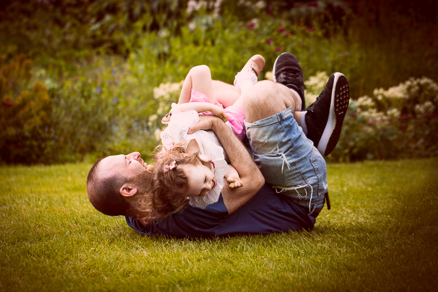 A dad catches his daughter after she ran towards him during a family photoshoot London