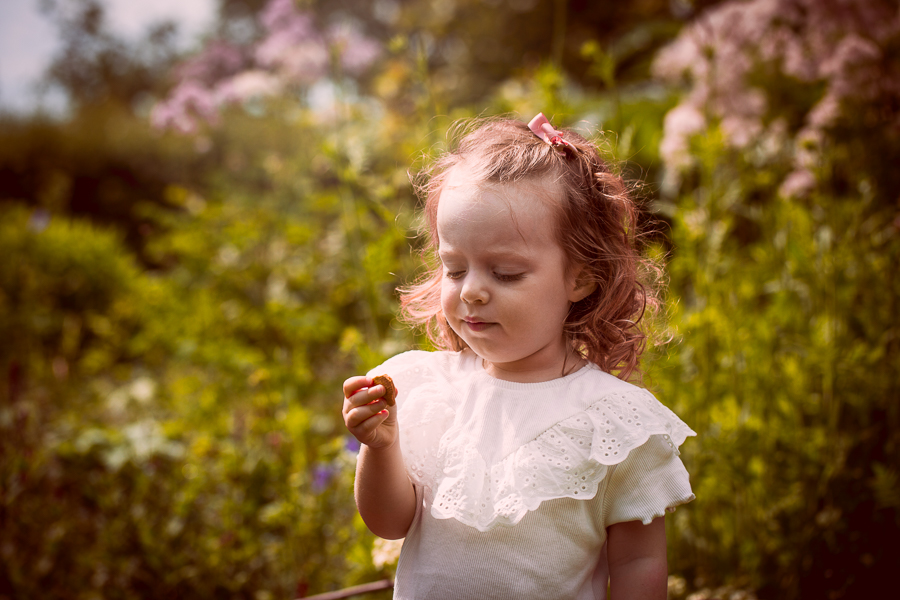 A girl eats a biscuit during a family photoshoot North London