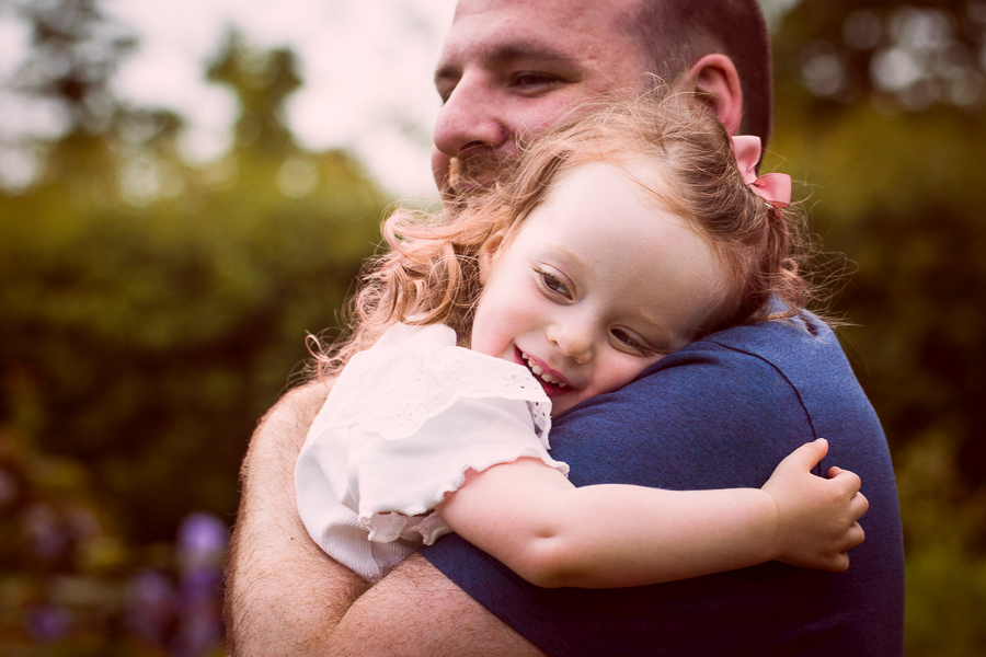 A dad hugs his little girl tight during a family photoshoot in north London